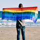 Man with a rainbow flag in front of the ocean