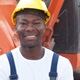 Black construction worker infront of a digger