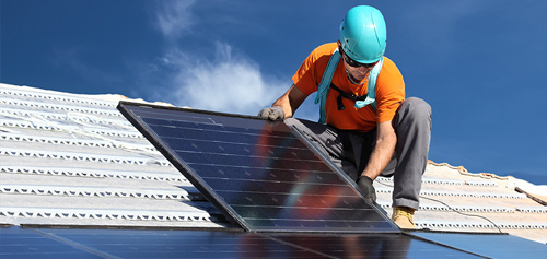 Man fitting solar panels on a roof