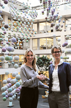 Brigitte Bloksma, director of Kasteel Wijlre, and Lianne Schipper, curator of the Aegon art collection, shake hands in front of Peter Struycken's three-dimensional Color Structure in the atrium of the Aegon headquarters in The Hague.